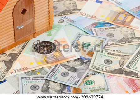 Plastic house on a pile of money - stock photo