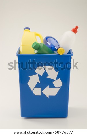 Plastic household materials in a blue recycling bin. White background. - stock photo