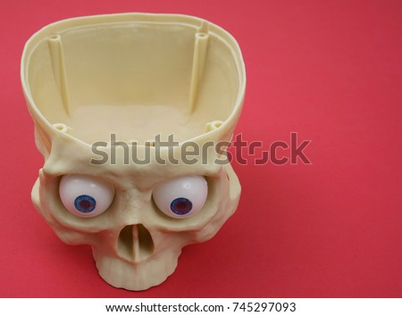 Plastic human skull and funny eyes on red paper background