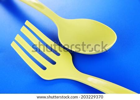 Plastic kitchen utensils on blue background - stock photo
