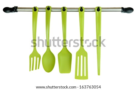 Plastic kitchen utensils on silver hooks isolated on white - stock photo