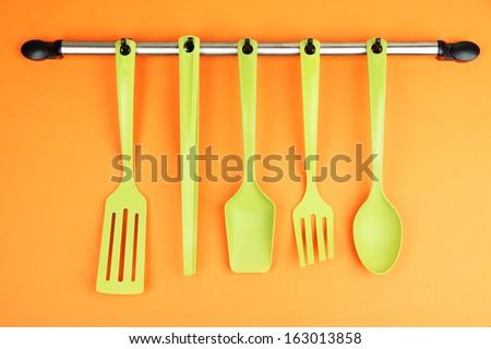 Plastic kitchen utensils on silver hooks on orange background - stock photo