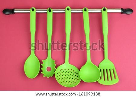 Plastic kitchen utensils on silver hooks on red background - stock photo
