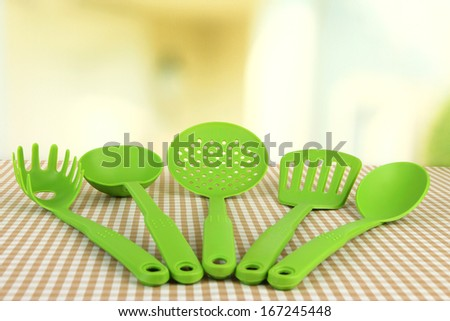 Plastic kitchen utensils on tablecloth on bright background - stock photo
