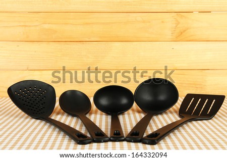 Plastic kitchen utensils on tablecloth on wooden background - stock photo