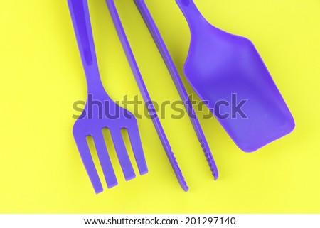 Plastic kitchen utensils on yellow background - stock photo