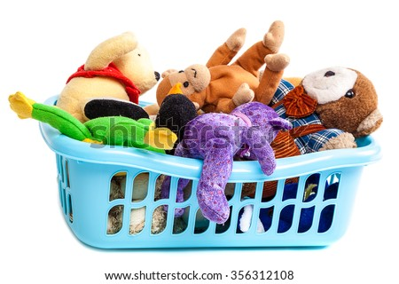 Plastic laundry basket with soft toys isolated on a white background.