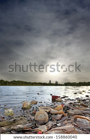 Plastic litter polluting a green environment against an apocalyptic sky.  - stock photo