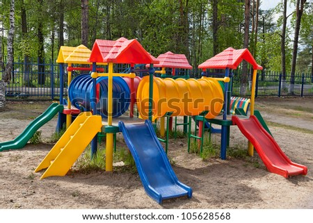 Plastic multi-colored children's playground in a pine park on a sunny day