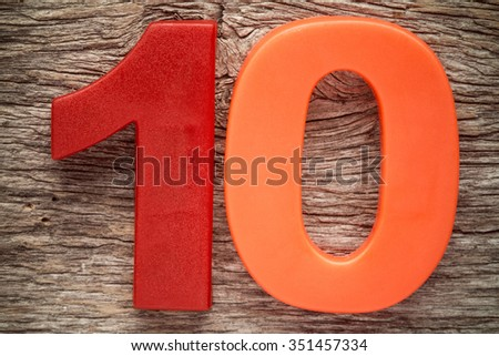 Plastic number ten on the wooden background - stock photo