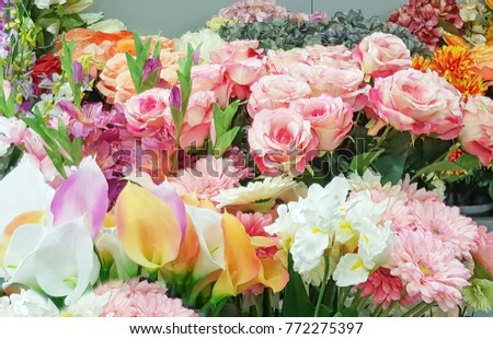 Plastic or fake colourful flowers. Background texture, Colorful decoration artificial flowers background.