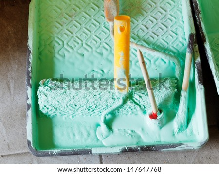 plastic paint tray with green emulsion paint and paintbrushes - stock photo