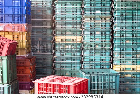 Plastic Pallets of Various Colors Pile Up Together And Form A Wall - stock photo