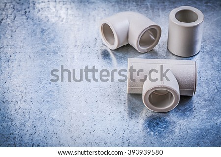 Plastic pipe connectors on metallic surface construction concept. - stock photo