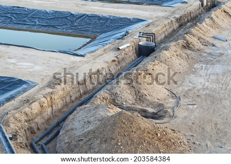 Plastic pipes being placed under ground for water supply for industrial site. - stock photo