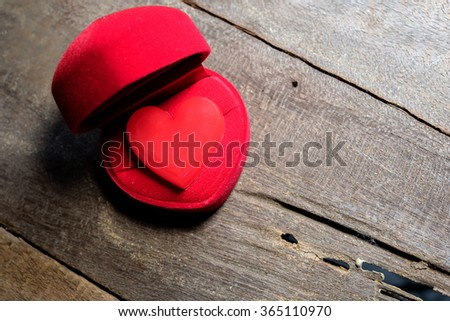 plastic red heart shape in box on wood floor