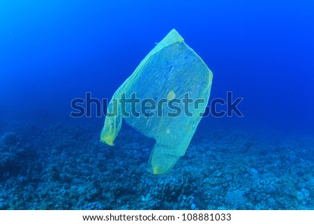 Plastic rubbish bag pollutes a coral reef in the ocean