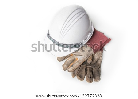Plastic safety helmet and Dirty old leather gloves on white background - stock photo