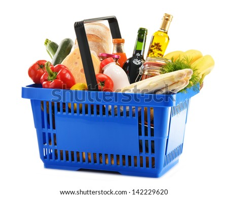 Plastic shopping basket with variety of grocery products isolated on white - stock photo