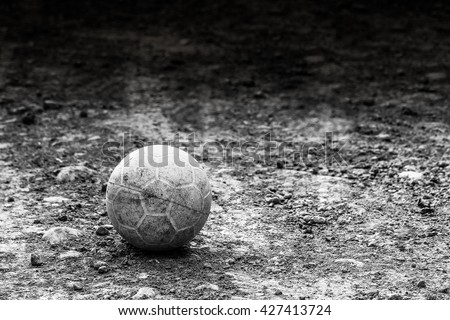 Plastic soccer ball on rocky ground  black and white background - stock photo