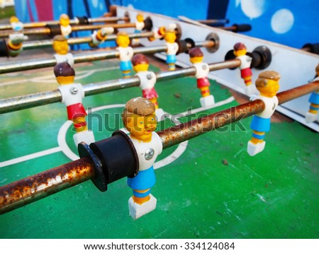 Plastic soccer players on poles on a rusty vintage foosball table.  - stock photo