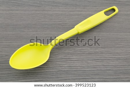 Plastic spoon on wooden table