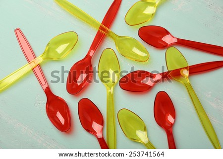 Plastic spoons on wooden background - stock photo