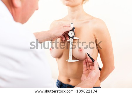 Plastic surgeon doctor measuring examine woman patient breast, prepare for operation silicon implants - stock photo