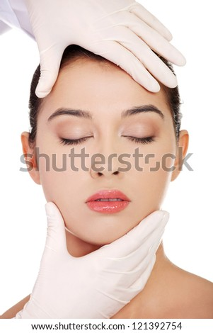 Plastic surgery concept. Doctor hands in gloves touching the beautiful woman face. Isolated on white - stock photo