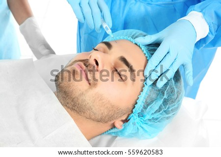 Plastic surgery concept. Doctor operating young man