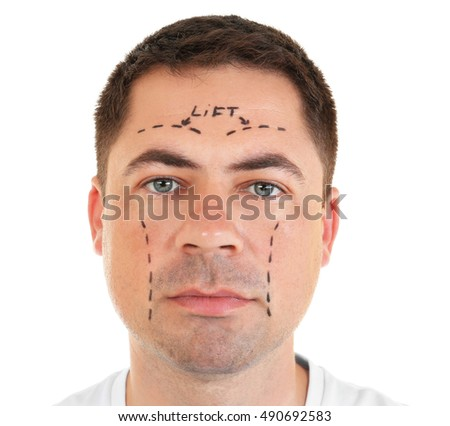 Plastic surgery concept. Portrait of handsome man with marking on face