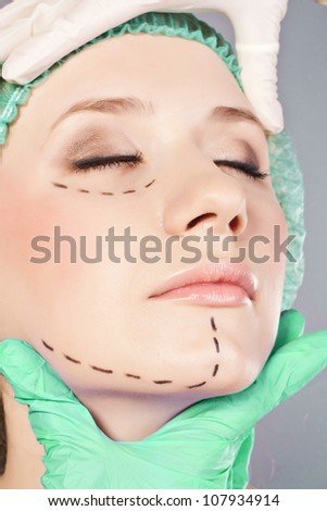 Plastic surgery hand touching the beautiful woman face.  Model is european beauty - stock photo