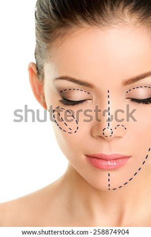 Plastic surgery lines on Asian woman face. Closeup of female adult with closed eyes with pencil marks on skin for cosmetic medical procedures. Surgical mark lines on eyes, nose, cheek, and jaw. - stock photo