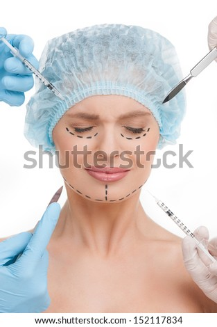 Plastic surgery. Terrified young woman keeping eyes closed while many hands holding syringes and scalpels near her face - stock photo