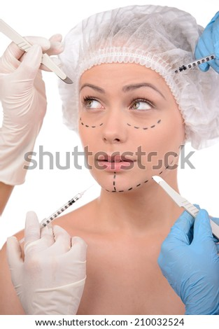 Plastic surgery. Terrified young woman looking away while many hands holding syringes and scalpels near her face - stock photo