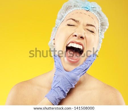 plastic surgery. woman scream. pain. studio - stock photo