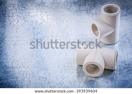 Plastic T-tube connectors on metallic background construction concept. - stock photo
