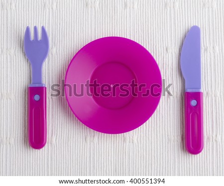 plastic tableware toys isolated on white cloth - stock photo