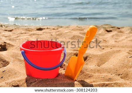 Plastic toy spade and bucket on sea beach
