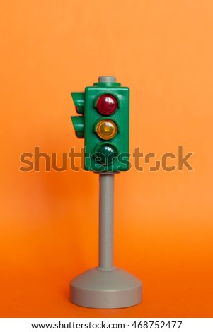 Plastic toy traffic lights on the orange background