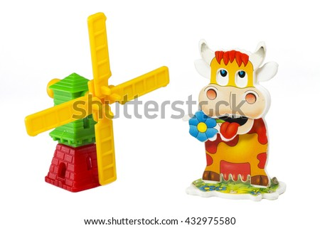 Plastic toy windmill and funny cow isolated on white background. - stock photo