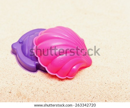 plastic toys on a sand - stock photo