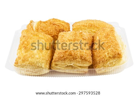 Plastic transparent box with flaky biscuits isolated on white background - stock photo