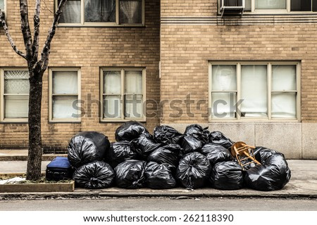 Plastic trash bags on curb outside city building - stock photo