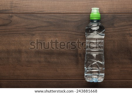 plastic water bottle on the wooden table - stock photo