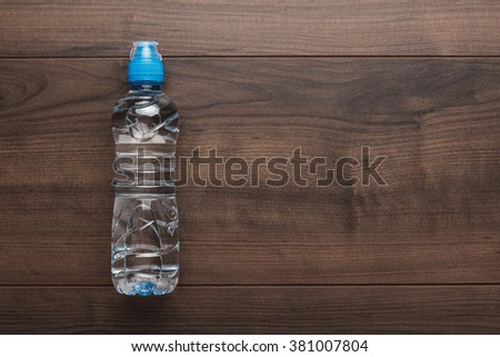 plastic water bottle with blue cap on the wooden table - stock photo