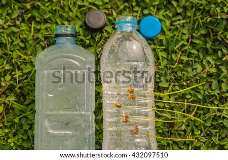Plastic water bottles on the grass creatures need water.  - stock photo