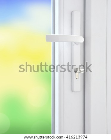 Plastic window with lock and bright blurred nature background - stock photo