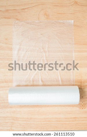 plastic wrap isolated on wood - stock photo