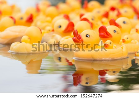 Plastic yellow duck toy with water reflection - stock photo
